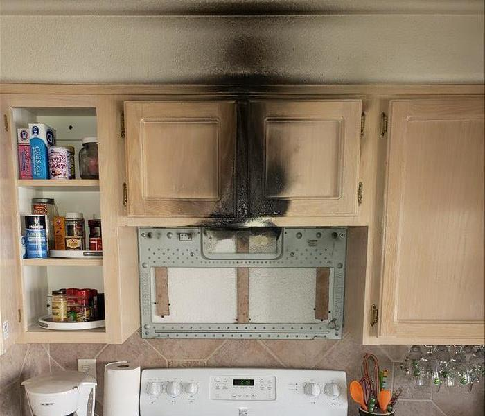 aftermath of a small kitchen fire caused by a mounted microwave.  Visible black smoke damage to upper cabinets and drywall