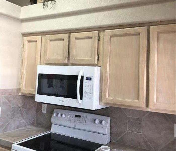 cleaned and restored kitchen cabinets and drywall.  Newly mounted microwave.