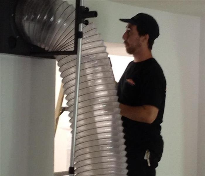 SERVPRO Tech Performing Professional Duct Cleaning using our Large Safe Self Contained Suction Method